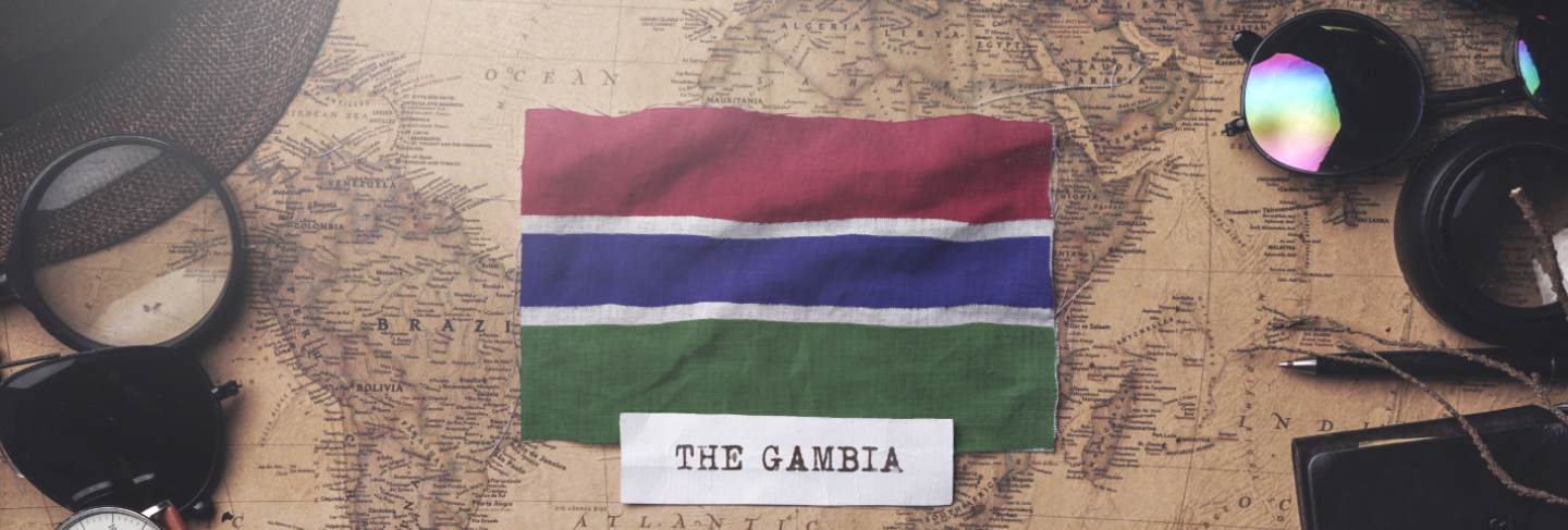 The gambia flag between traveler's accessories on old vintage map. overhead shot