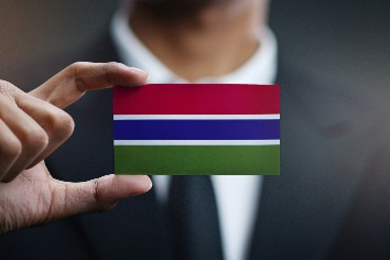Businessman holding card of the gambia flag