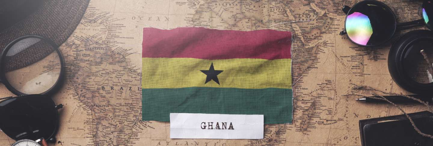 Ghana flag between traveler's accessories on old vintage map. overhead shot