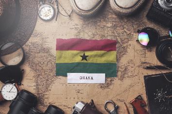 Ghana flag between traveler's accessories on old vintage map. overhead shot
