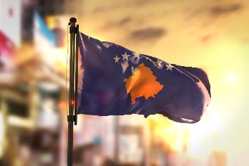 Kosovo flag against city blurred background at sunrise backlight