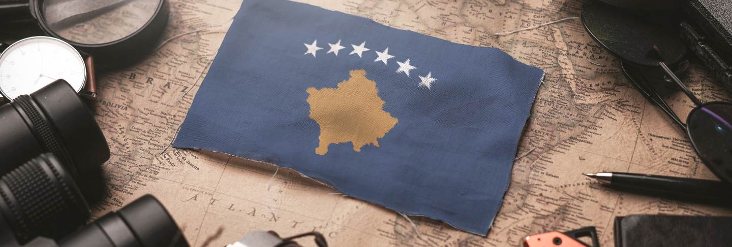Kosovo flag between traveler's accessories on old vintage map. tourist destination concept.