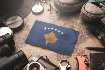 Kosovo flag between traveler's accessories on old vintage map. tourist destination concept.