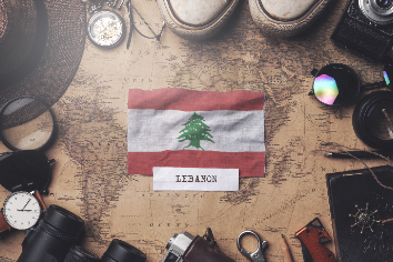Lebanon flag between traveler's accessories on old vintage map. overhead shot