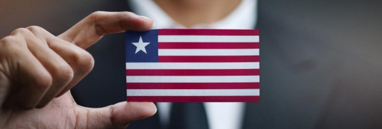 businessman-holding-card-liberia-flag_1379-3117