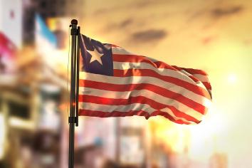 liberia-flag-against-city-blurred-background-sunrise-backlight_1379-1567