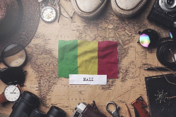 Mali flag between traveler's accessories on old vintage map. overhead shot