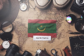 Mauritania flag between traveler's accessories on old vintage map. overhead shot