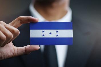 Businessman holding card of honduras flag