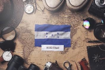 Honduras flag between traveler's accessories on old vintage map. overhead shot