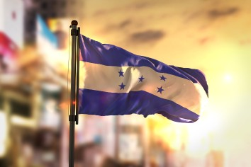 Honduras flag against city blurred background at sunrise backlight