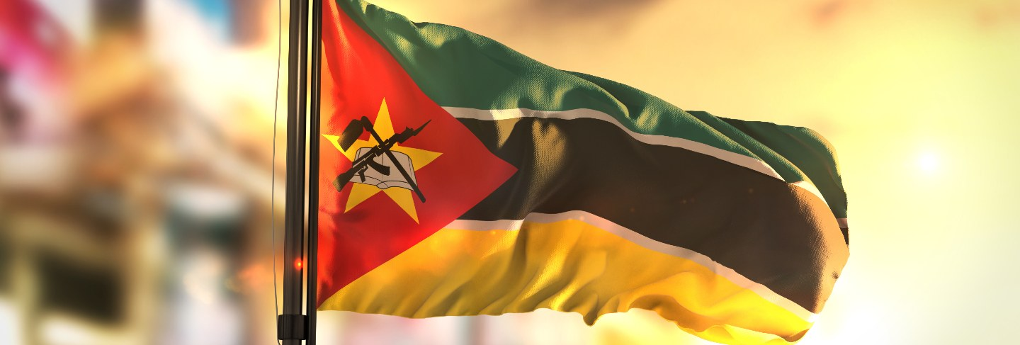 Mozambique flag against city blurred background at sunrise backlight
