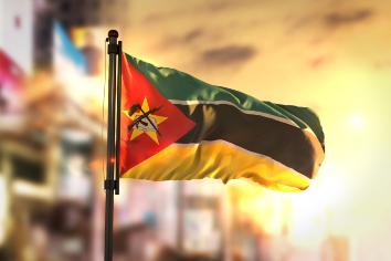 Mozambique flag against city blurred background at sunrise backlight