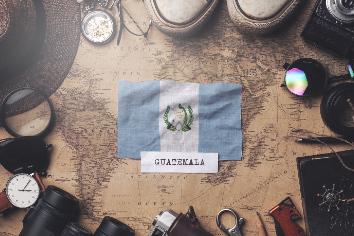 Guatemala flag between traveler's accessories on old vintage map. overhead shot