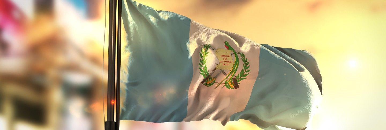 Guatemala flag against city blurred background at sunrise backlight