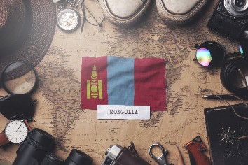 Mongolia flag between traveler's accessories on old vintage map. overhead shot