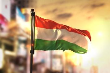 Hungary flag against city blurred background at sunrise backlight