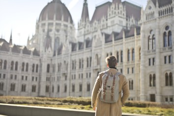 Male wearing brown coat and backpack near hungarian parliament building in budapest