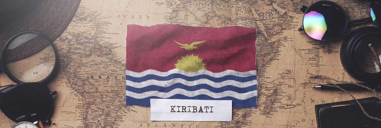 Kiribati flag between traveler's accessories on old vintage map