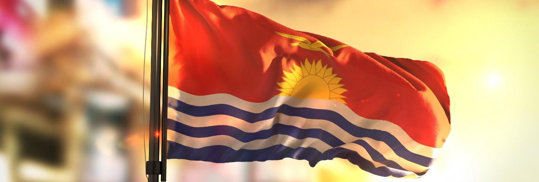 Kiribati flag against city blurred background at sunrise backlight