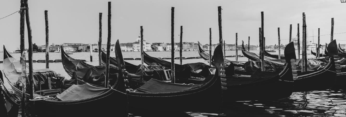 Black and white shot of gondolas docked in the water