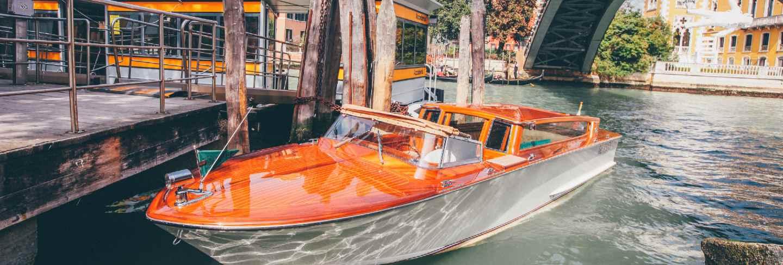 Orange waterway boat on a river under a bridge near buildings in venice, italy