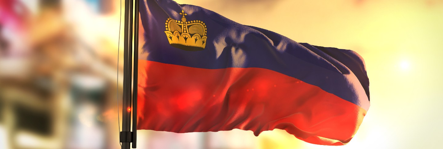 Liechtenstein flag against city blurred background at sunrise backlight