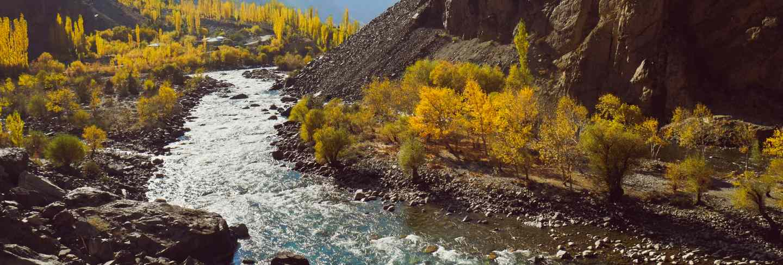 Winding river flowing along valley in hindu kush mountain range. autumn season in pakistan Premium Photo