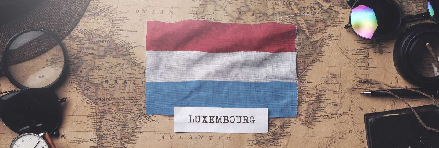 Luxembourg flag between traveler's accessories on old vintage map. overhead shot