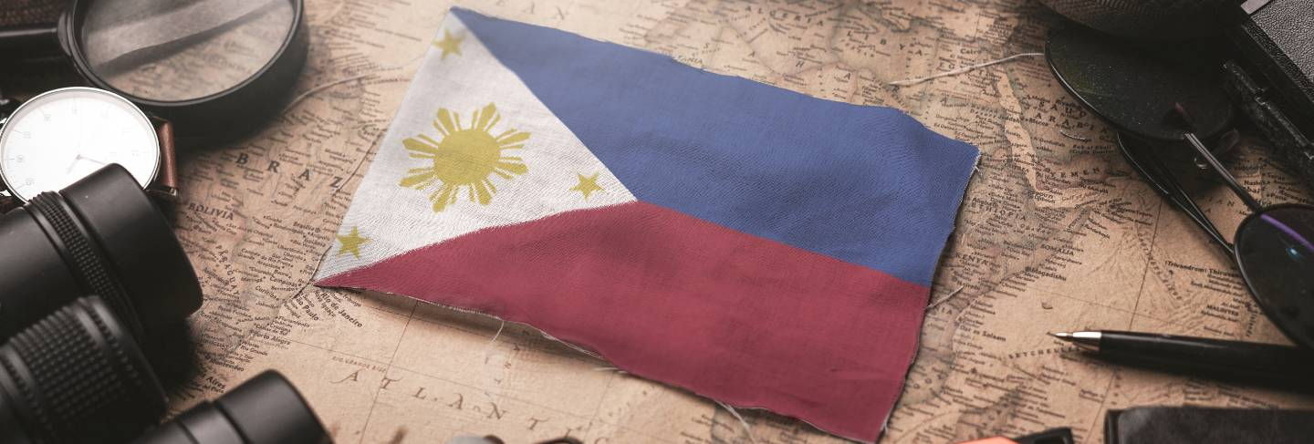 Philippines flag between traveler's accessories on old vintage map. tourist destination concept