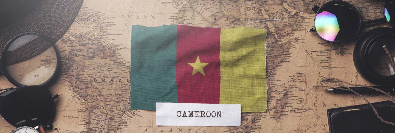 Cameroon flag between traveler's accessories on old vintage map. overhead shot