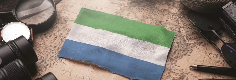 Sierra leone flag between traveler's accessories on old vintage map. tourist destination concept.