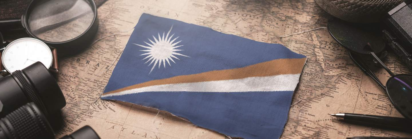 Marshall islands flag between traveler's accessories on old vintage map. tourist destination concept