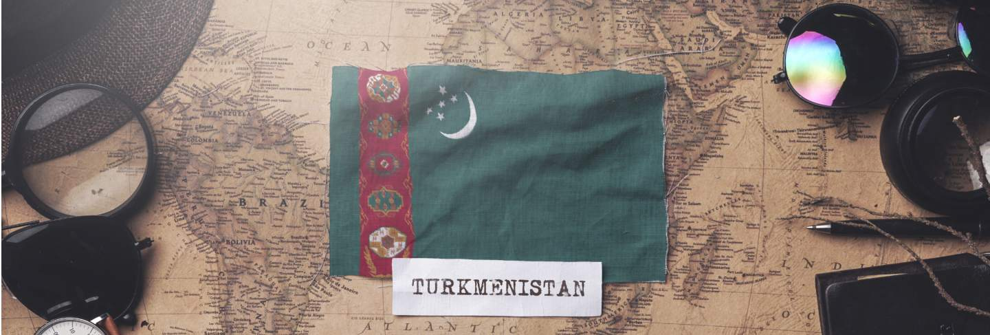 Turkmenistan flag between traveler's accessories on old vintage map. overhead shot