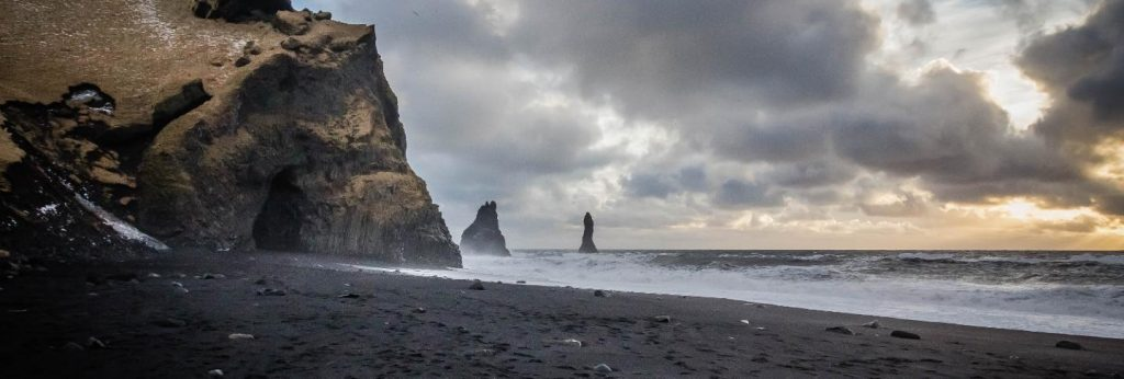 Beautiful coast of the sea at vik, iceland with breathtaking clouds and rocks on the side