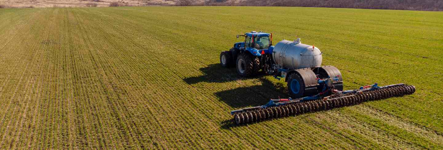 Tractor applying liquid mineral fertilizers to the soil on winter wheat