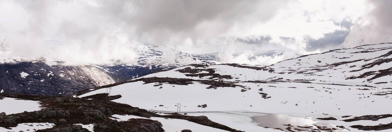 Snow lies before blue rock summints in norway