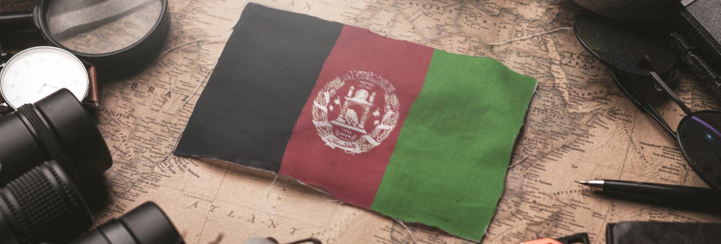 Afghanistan flag between traveler's accessories on old vintage map. tourist destination concept