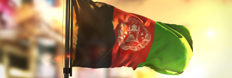 Afghanistan flag against city blurred background at sunrise backlight