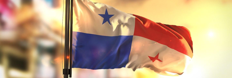 Panama flag against city blurred background at sunrise backlight