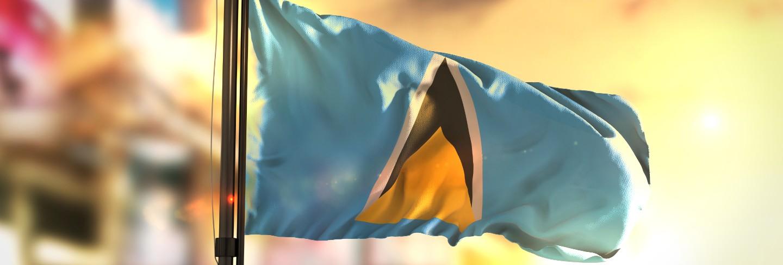 Saint lucia flag against city blurred background at sunrise backlight