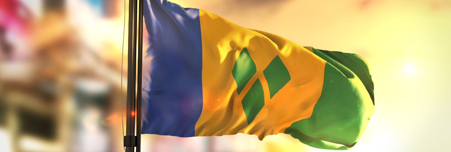 Saint vincent and the grenadines flag against city blurred background at sunrise backlight