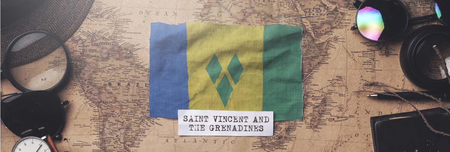 Saint vincent and the grenadines flag between traveler's accessories on old vintage map.