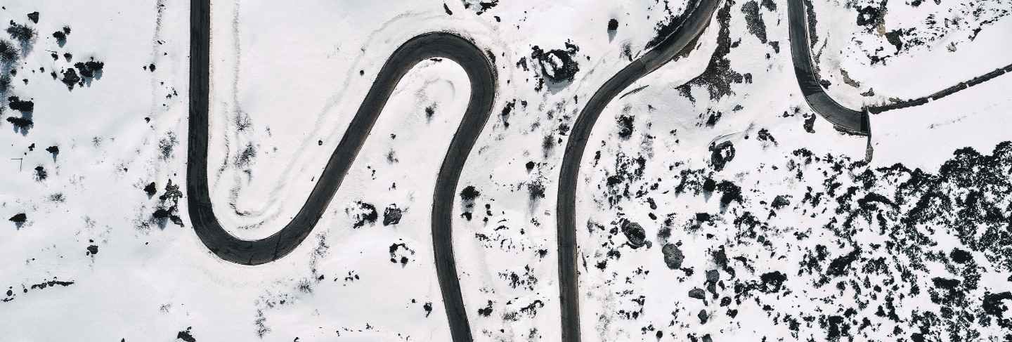 Aerial shot of a beautiful snowy field with a curved road in the middle