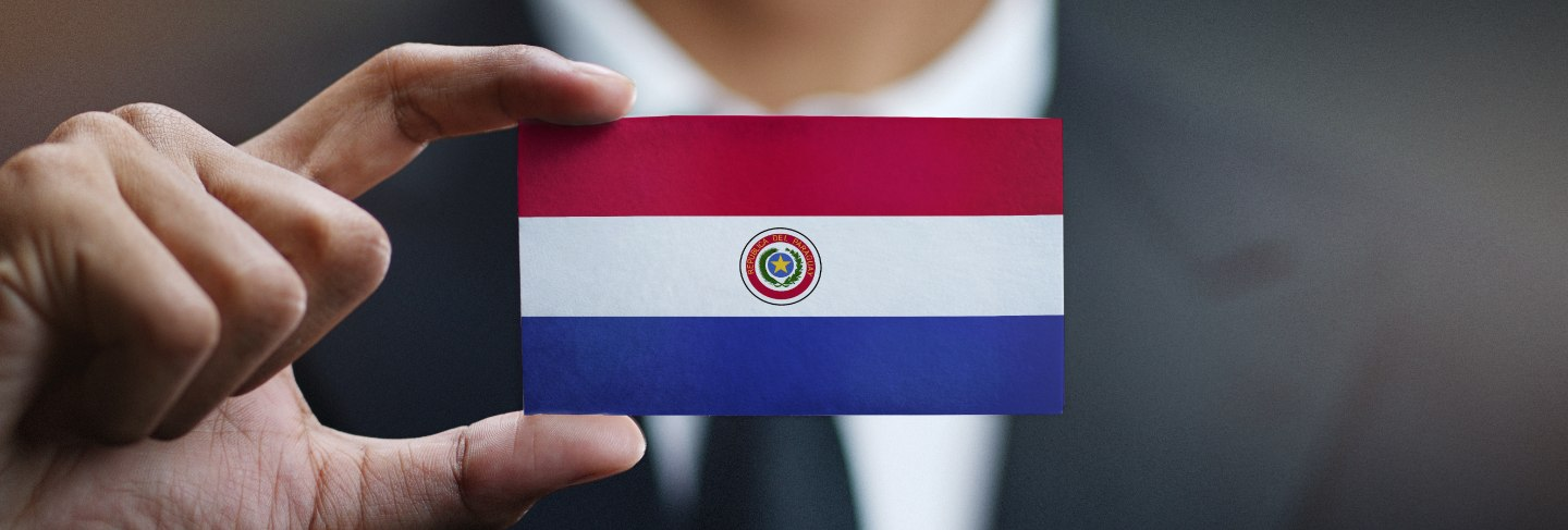 Businessman holding card paraguay flag