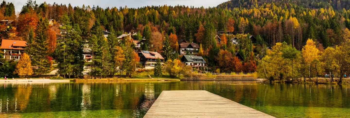 Wooden pier on amazing lake jasna in autumn season, slovenian alps