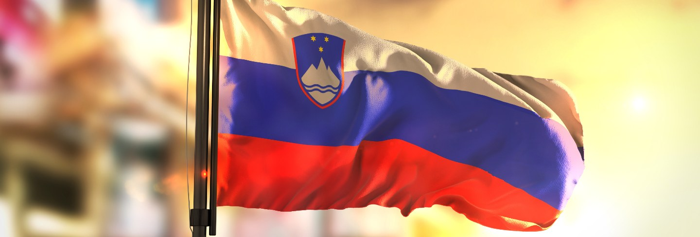 Slovenia flag against city blurred background at sunrise backlight