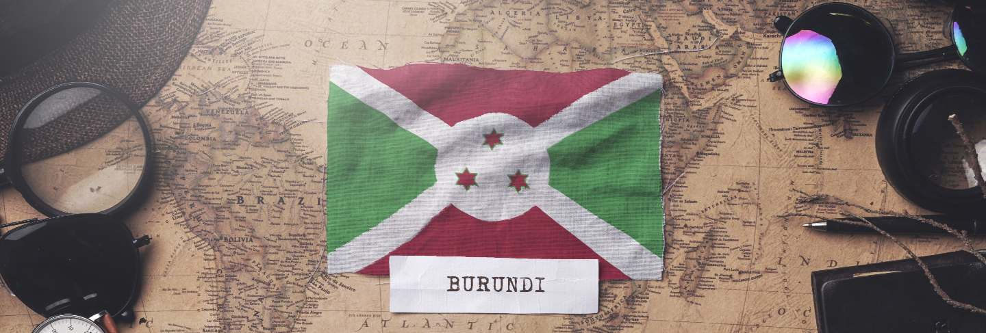 Burundi flag between traveler's accessories on old vintage map.