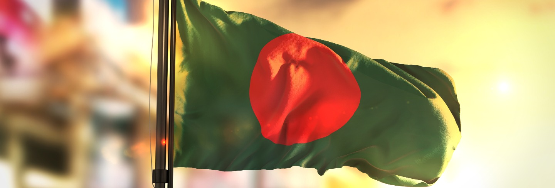 Bangladesh flag against city blurred background at sunrise backlight