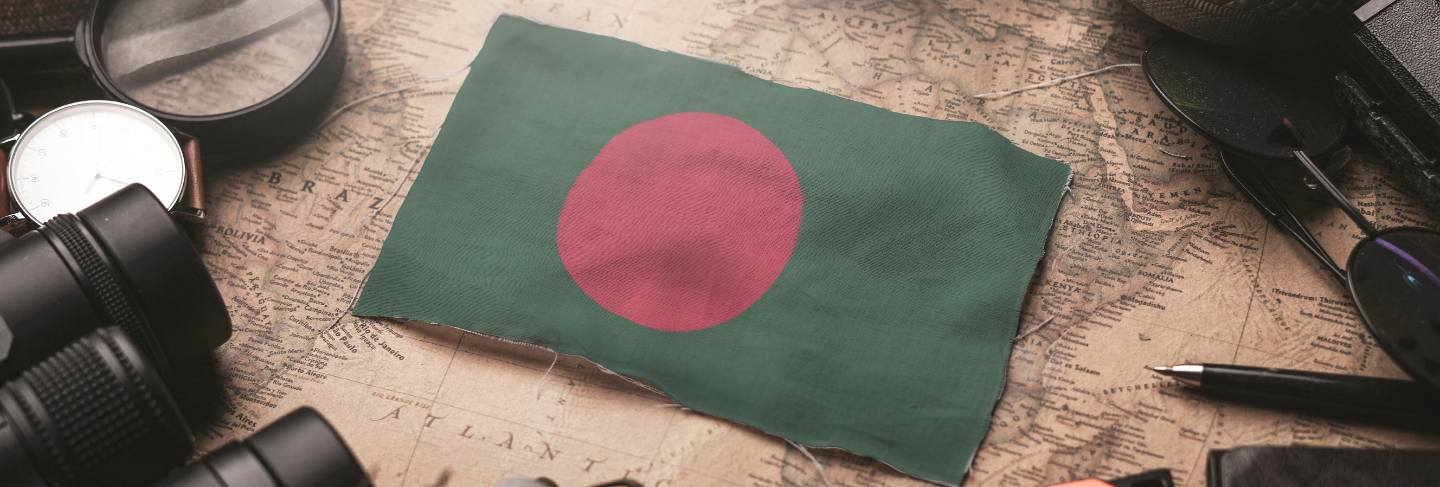 Bangladesh flag between traveler's accessories on old vintage map. tourist destination concept.